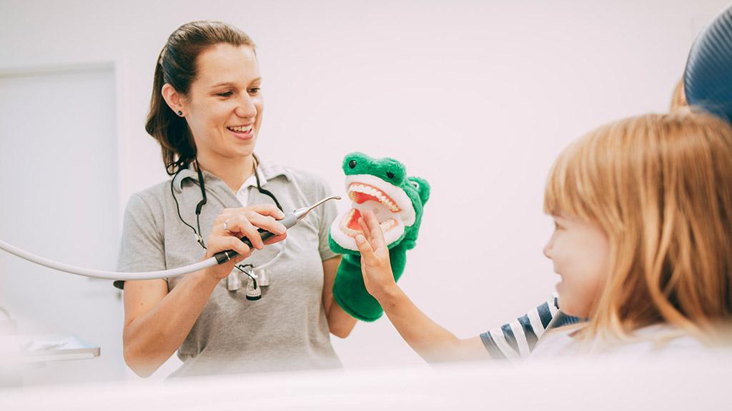 Zahnärztin aus Bonn-Oberkassel zeigt Kind die richtige Zahnprophylaxe.