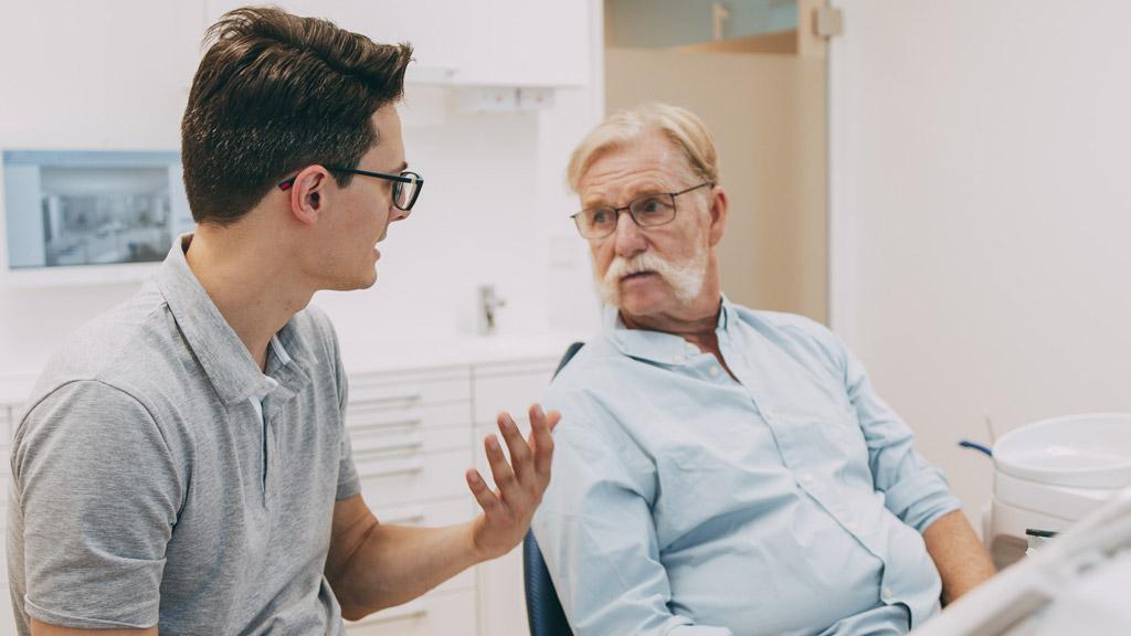 Dr. Gero Winkler erklärt Patienten den Ablauf der Parodontosebehandlung in Bonn-Oberkassel.